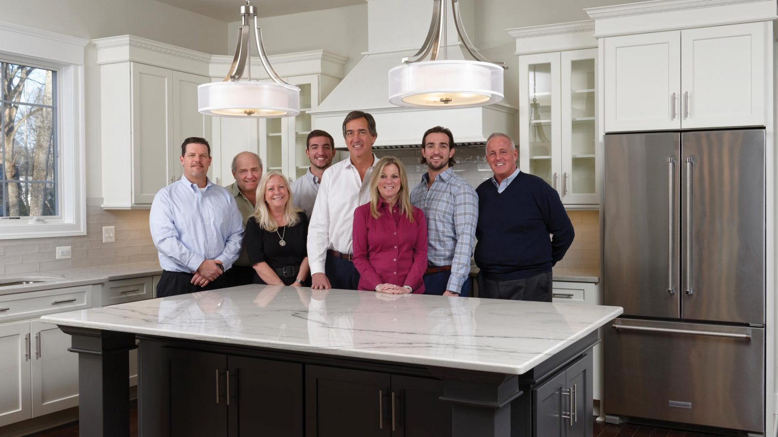 Picture of the Sekas Homes team standing in a large, modern kitchen